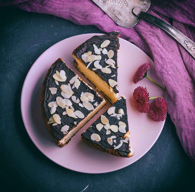 Pieces of cheesecake with chocolate on a pink plate