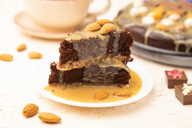 Pieces of chocolate brownie cake with caramel cream and almonds on a white concrete background.