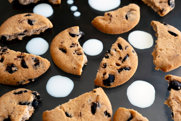 Pieces of chocolate chip cookies with milk drops on black background