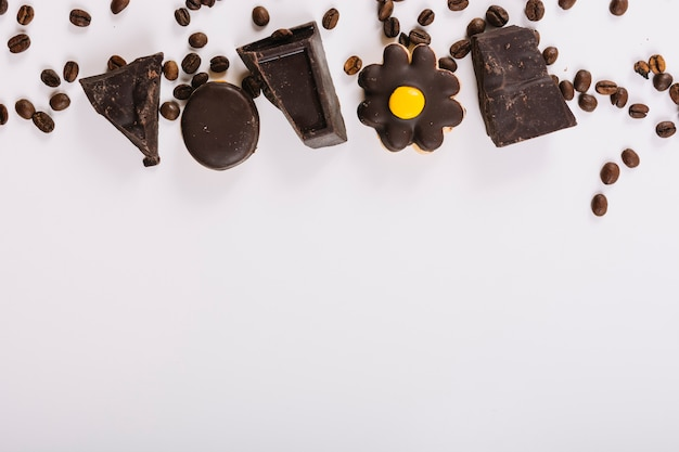 Pieces of chocolate between coffee beans