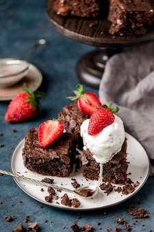 Pieces of chocolate nut brownie, with scoop of ice cream, on white plate, spoon, with slices of strawberries, crumbs, grey textile. dark blue background. vertical