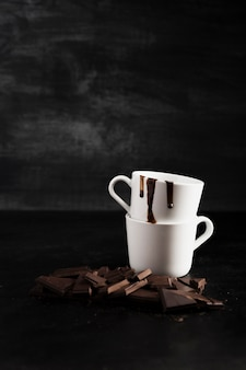 Pieces of chocolate and pile of mugs