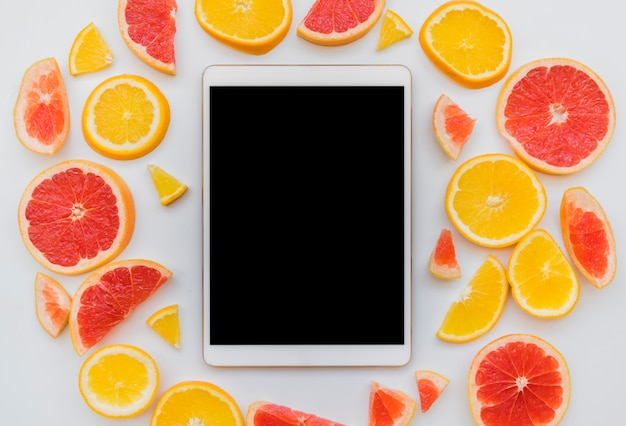 Pieces of citrus fruits around digital tablet