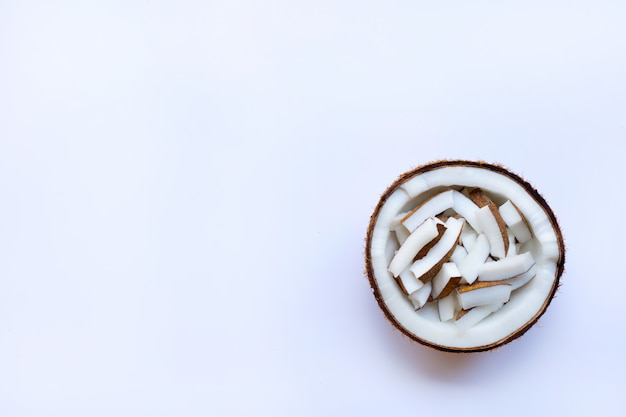 Pieces of coconut in half coconut on white background.