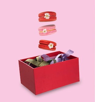 Pieces of colorful macaroons or french macarons levitating on red gift box filled with colorful ribbons. isolation on pink background.  levitating food photography.