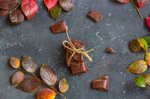 Pieces of dark chocolate and fall leaves on a dark . candy sweet dessert and snack. dark chocolate is an antioxidant and boosts energy and serotonin. close up, copyspace