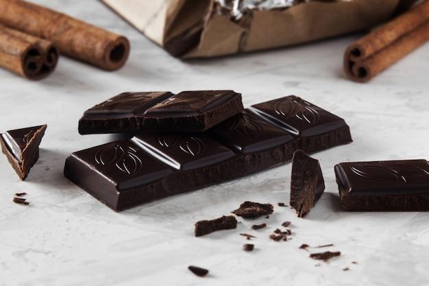 Pieces of dark chocolate with cinnamon sticks