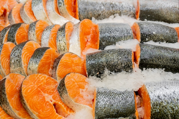 Pieces of fish lie in ice. fresh salmon steaks  sale in supermarket. salmon slices on store window. gourmet seafood.