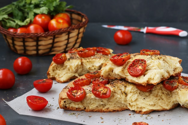 Pieces of focaccia with cherry tomatoes are located on parchment on a dark surface