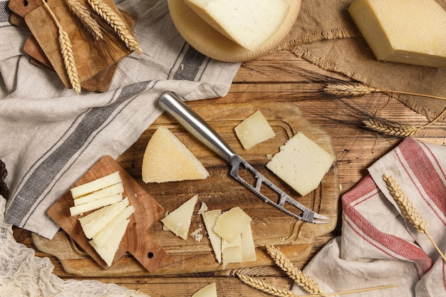 Pieces of  fresh homemade cheese on a wooden board with a knife  top view