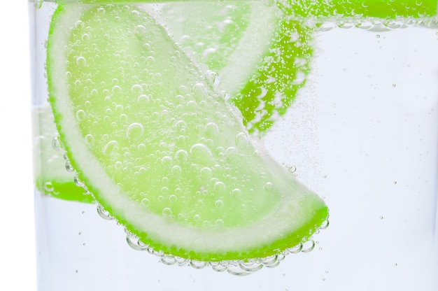 Pieces of fresh juicy lime sink into crystal clear water.