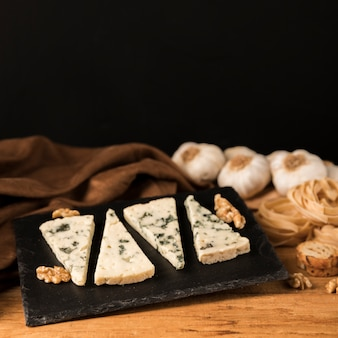 Pieces of gorgonzola cheese on black stone with walnut and garlic over desk