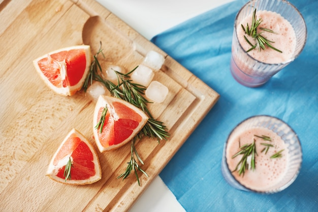 Pieces of grapefruit and rosemary on wooden desk. healthy detox diet smoothie.fitness weigth loss concept. from above.