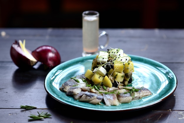 Pieces of herring with green onions, fried potatoes and cheese