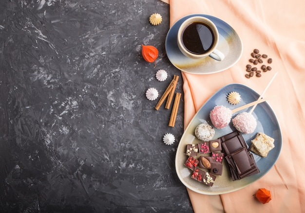 A pieces of homemade chocolate with coconut candies and a cup of coffee. top view