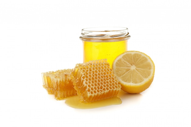 Pieces of honeycomb, glass jar and lemon isolated on white background