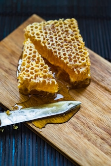 Pieces of honeycomb and knife on wooden chopping board