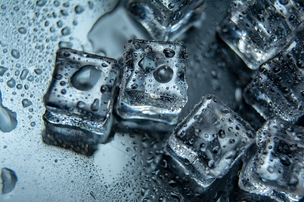 Pieces of ice cubes with water droops on black-mirrow background.