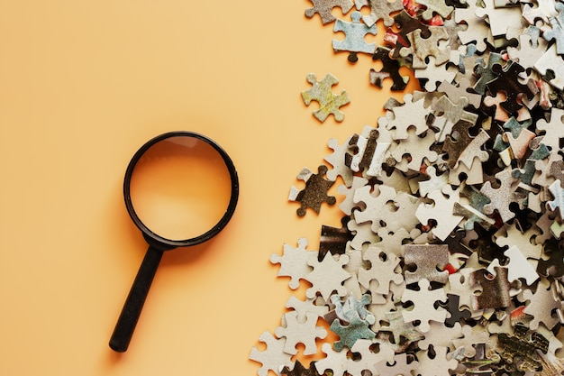 Pieces of jigsaw puzzle with magnifying glass on beige color background
