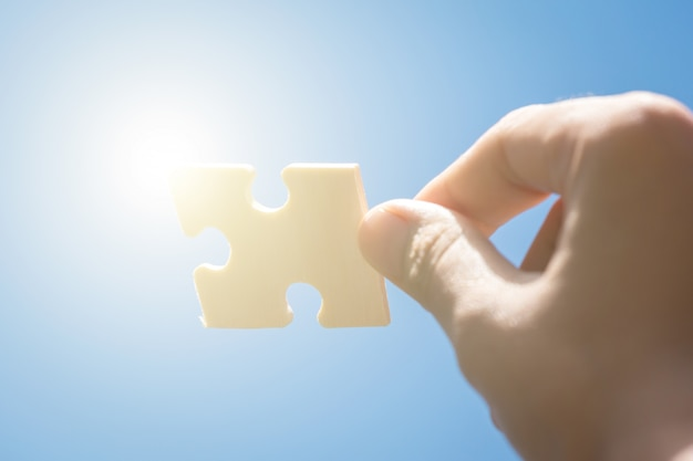 Pieces of jigsaw puzzle in woman's hands with blue sky background