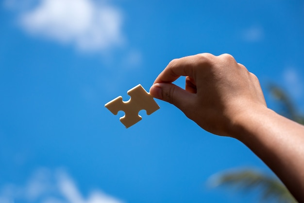 Pieces of jigsaw puzzle in woman's hands with blue sky