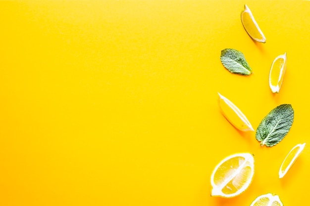 Pieces of lemon, lime and green mint leaves on a yellow background.