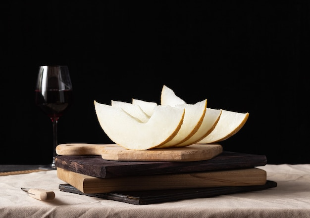 Pieces of melon on a wooden board, a glass of wine on the background. rustic style.