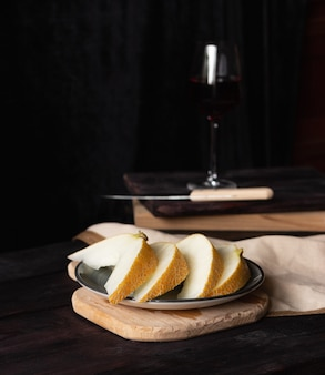 Pieces of melon on wooden boards with a knife, a glass of wine on the background. rustic style.