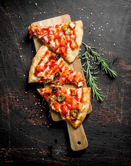 Pieces of mexican pizza on wooden cutting board with rosemary on dark rustic table