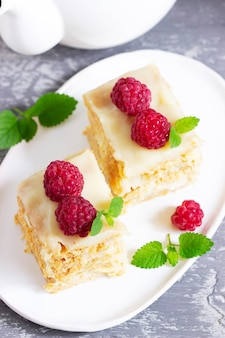 Pieces of napoleon cake decorated with raspberries and lemon balm leaves on a light background. selective focus.