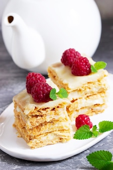 Pieces of napoleon cake decorated with raspberries and lemon balm leaves on a light background.