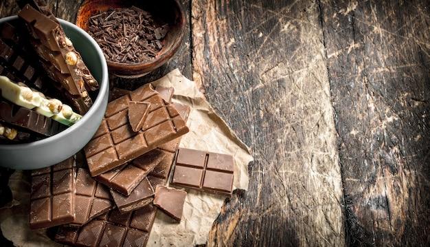 木製のテーブルのボウルに削りくずが入った別の種類のチョコレートのかけら。
