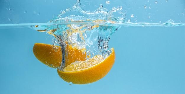 食欲をそそる熟したオレンジのかけらが澄んだ水に落ちて、たくさんの水しぶきを形成しています