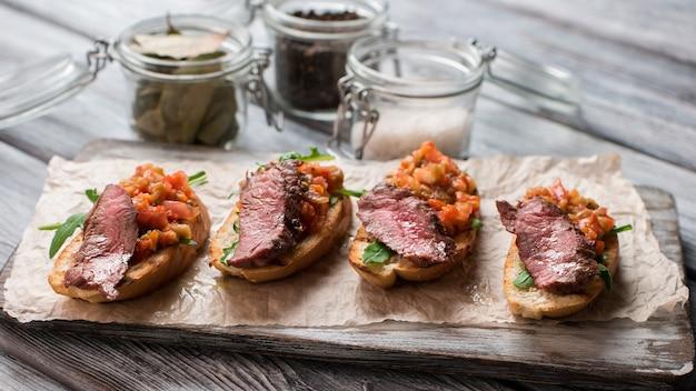 고기와 바게트 조각입니다. 구운 야채와 허브. 육즙이 풍부한 송아지 고기를 곁들인 브루스케타. 미식가를 위한 음식.