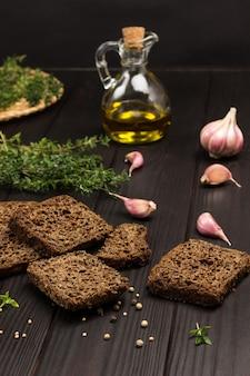 黒パン、タイムの小枝、ガラス瓶に入った油、テーブルの上のニンニク。上面図