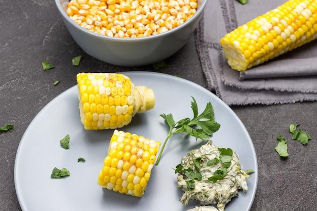 Кусочки вареной кукурузы, соус на серой тарелке. зерна кукурузы в миске. черный фон. вид сверху