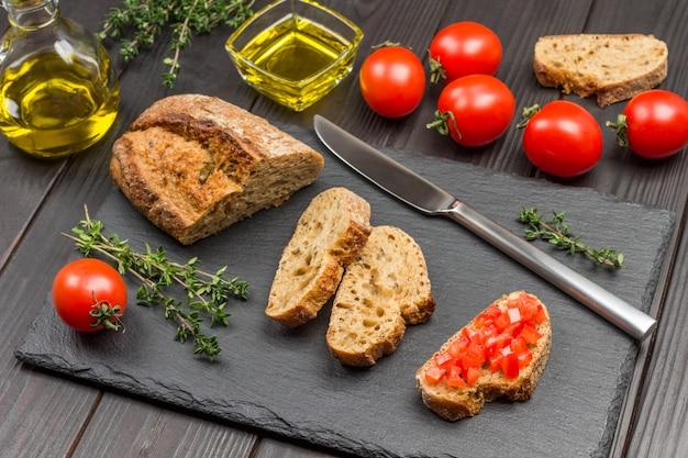 パンとナイフのかけら。スライスしたトマトサンドイッチ。テーブルの上のトマト、オリーブオイル、タイムの小枝。パーティースターターまたは前菜。上面図