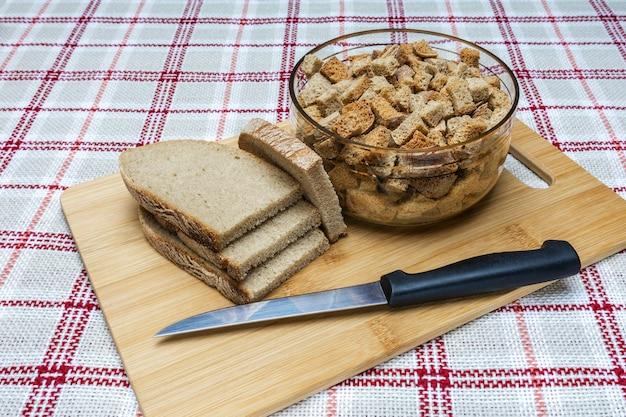 Кусочки хлеба для приготовления сухарей лежат на разделочной доске
