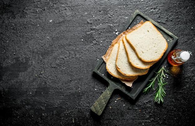 Кусочки хлеба на разделочной доске с розмарином и маслом. на черном деревенском фоне