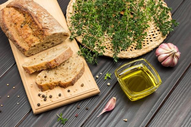 まな板の上のパンの断片。枝編み細工品プレートのタイム小枝。ガラスのボウルに油を入れ、テーブルにニンニクを入れます。上面図