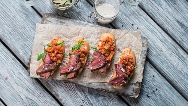 고기와 빵 조각입니다. 작은 샌드위치의 상위 뷰입니다. 갓 구운 브루스케타. 전통적인 이탈리아 식사입니다.