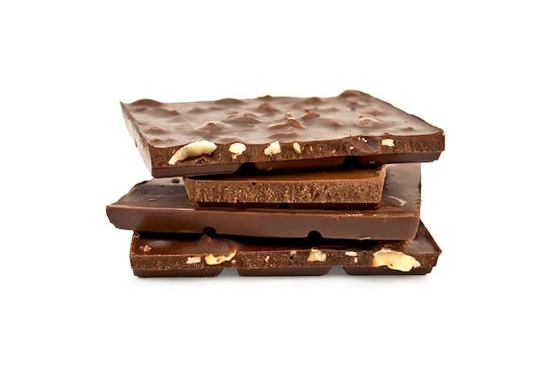 Кусочки битого темного шоколада с орехами и молочным шоколадом, изолированные на белом фоне
