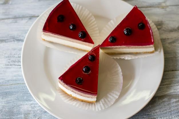 접시에 케이크 조각입니다. 건포도 장식 디저트. 젤리를 넣은 치즈케이크. 천연 성분과 검증된 레시피.