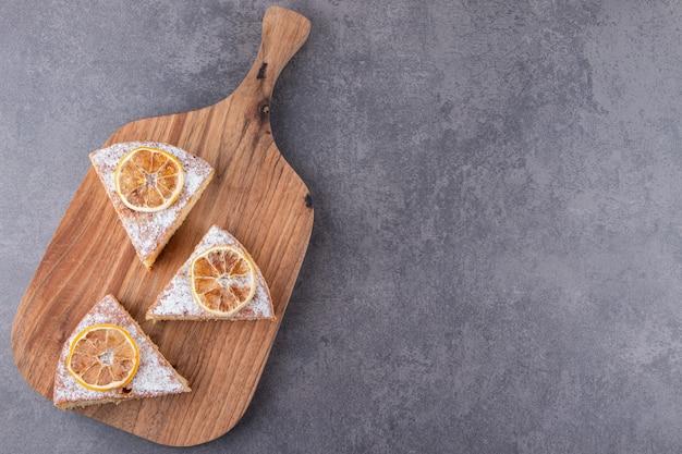 말린 레몬 조각과 케이크 조각을 돌 테이블에 놓습니다.