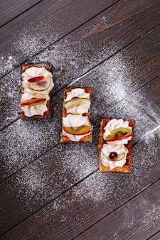 Кусочки торта с фруктами, покрытыми сахарной пудрой, подаются на деревянный стол