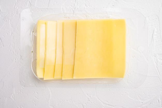 チェダーチーズセット、プラスチックパック、白い石のテーブル、上面図フラットレイ