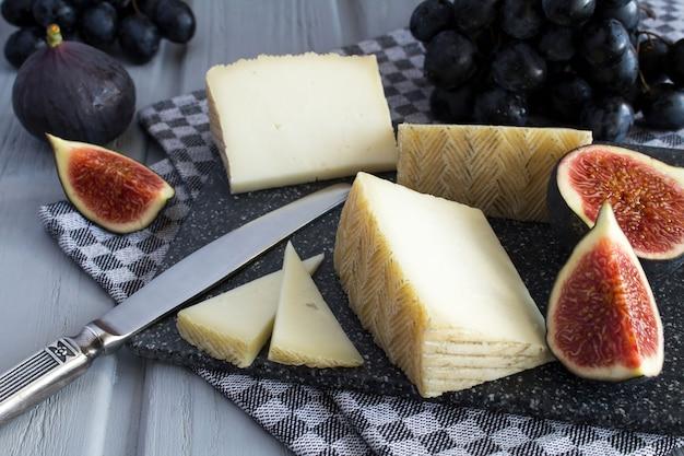 Кусочки сыра и фруктов на серой разделочной доске