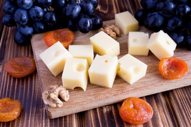 チーズ、ドライアプリコット、まな板の上の黒ブドウ