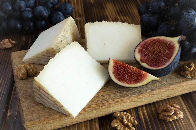 茶色のまな板にチーズ、ナッツ、フルーツの部分