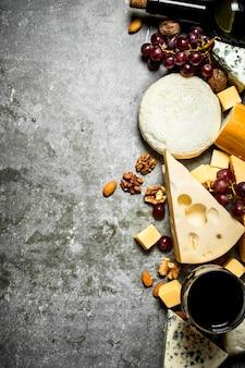 레드 와인과 견과류와 치즈 조각. 돌 테이블에.